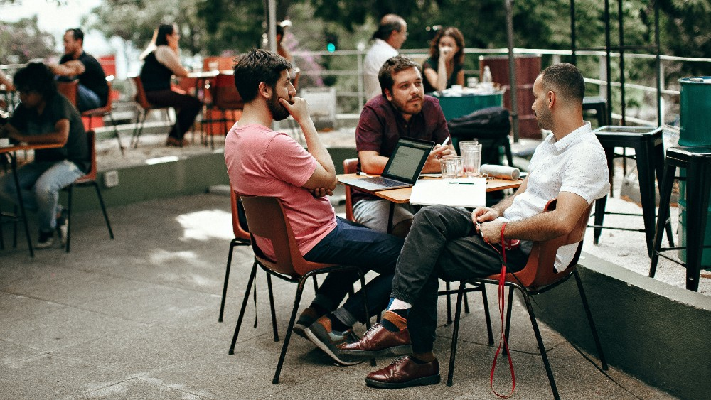 Three men sitting at a table outside while having a meeting