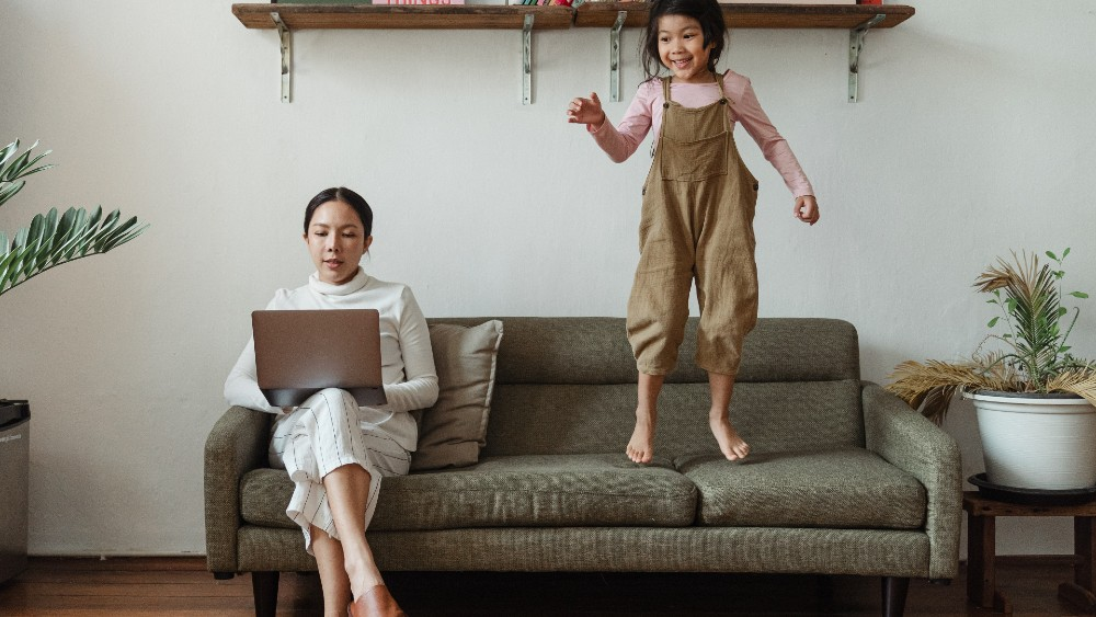 Woman working on couch with daughter standing on couch next to her